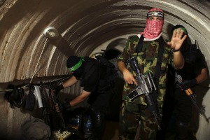 A Palestinian fighter from the Izz el-Deen al-Qassam Brigades, the armed wing of the Hamas movement, gestures inside an underground tunnel in Gaza August 18, 2014. A rare tour that Hamas granted to a Reuters reporter, photographer and cameraman appeared to be an attempt to dispute Israel's claim that it had demolished all of the Islamist group's border infiltration tunnels in the Gaza war. Picture taken August 18, 2014. REUTERS/Mohammed Salem (GAZA - Tags: POLITICS CONFLICT TPX IMAGES OF THE DAY) - RTR42YJW