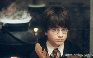 "RADCLIFF...TO GO WITH STORY TITLED POTTER COUNTDOWN--FILE--Actor Daniel Radcliffe writes with a quill in a scene from Warner Bros. ""Harry Potter and the Philosopher's Stone,"" in this undated promotional photo. The film has its world premiere in London this weekend and hits theaters Nov. 16. Based on the first of author J.K. Rowling's best-selling series, the movie follows the adventures of Harry, an orphan boy who is invited to become a student at the Hogwart's School of Witchcraft and Wizardry. The movie faces huge expectations not only among fans, but at the box office, too. (AP Photo/Warners Bros. Pictures, Peter Mountain/FILE)"